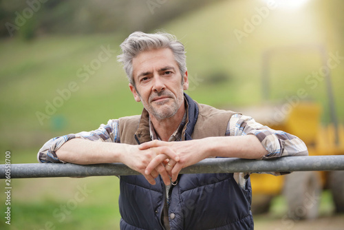 Foto Attractive farmer leaning on fence looking at camera