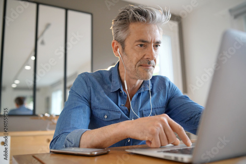 Photo  Mature man on video call working from home