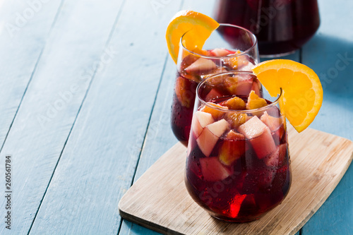 Cuadros en Lienzo Red wine sangria in glass on blue wooden table. Copyspace