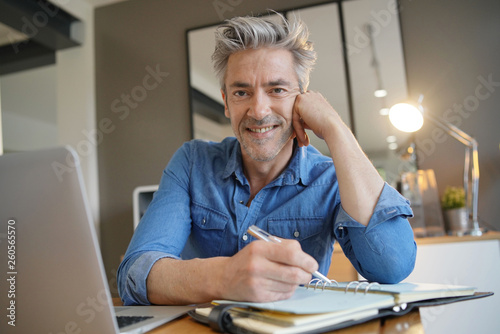 Photo  Mature man working from home smiling at camera
