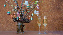 Branches With Flowers And Buds. Easter Eggs And Easter Bunnies Hang On The Branches. Sparkling Wine Bubbles In 2 Champagne Glasses.