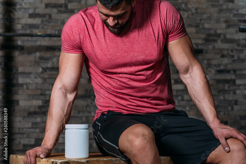 Fotografia  Muscular man holding sport nutrition products