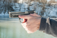 Shooter Holding Gun And Shooting On Winter Lake Water Background