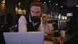 4K Bar Owner Working On Laptop With Female Employee Working In Background