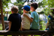 Three boys friends sitting on a log in the summer in the park. Three brothers together