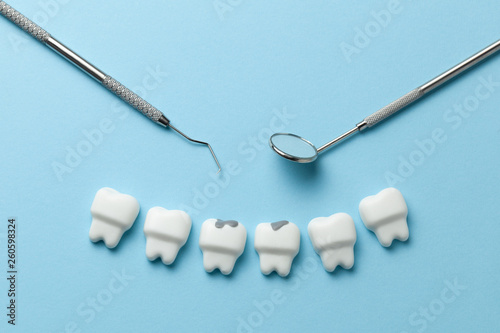Fotografia  White tooth with caries on blue background  and dentist tools mirror, hook