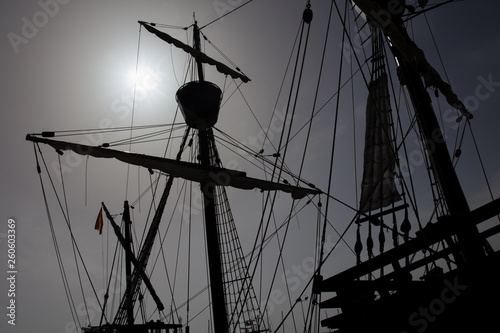 Valokuva  A caravel, an old sailing ship in front of the bright sun in the back light