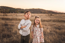 Young Girl And Boy With Goofy Smiles In California Field At Sunset
