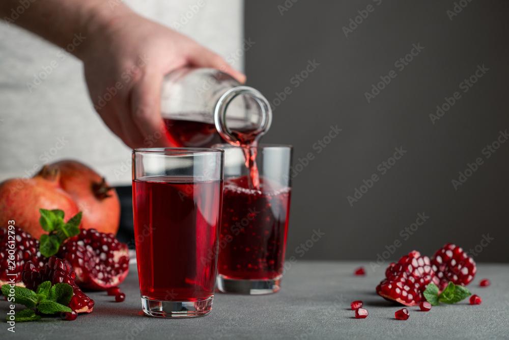 Fototapeta Male hand pouring pomegranate juice into a glass.