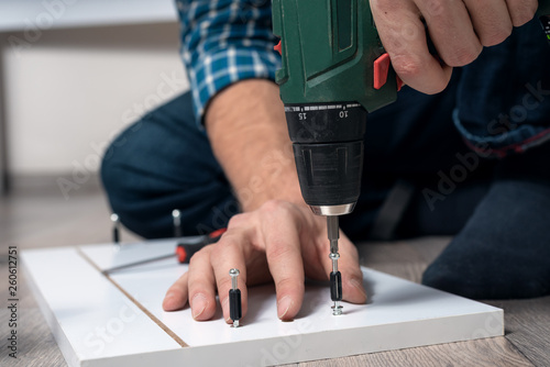 close-up of male hands assembling furniture with a screwdriver Fototapet