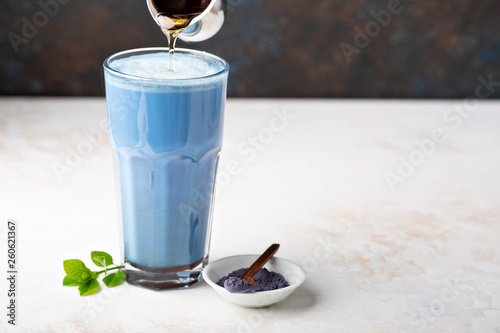 Obraz na płótnie Blue matcha latte in tall glass, tea from the dried flowers of the butterfly pea