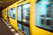 Yellow Blurred Subway Train In Berlin. Public U-bahn Transport In Underground Station Interior