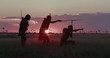 4K spectacular side view of three San people/Bushman in traditional dress at sunset looking for animals out on the Makgadikgadi grasslands, Botswana