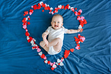 Cute Smiling White Caucasian Baby Girl Boy Infant With Blue Eyes Four Months Old Lying On Bed Among Many Foam Paper Red Pink Colorful Hearts. View From Top Above. Happy Valentine Day