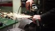 Worker man using circular saw to polish steel tube in car service, workshop. Polishing generates bright sparks. Slow motion.