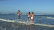4K rear view of two beautiful young woman and a young man laughing and running out of the sea, South Africa