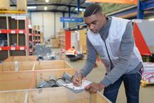 Worker Filling In Paperwork On Clipboard In Plumbing Hardware Store