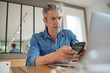 Mature man working from home looking at cellphone
