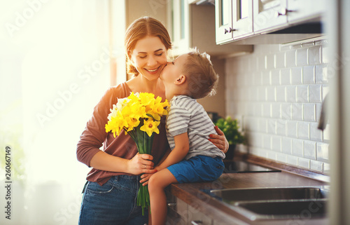 happy mother's day! child son gives flowersfor mother on holiday