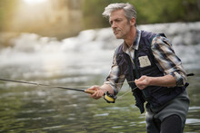 Mature Man Fly Fishing In Beau...