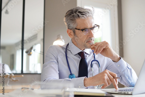 Cuadros en Lienzo  Mature doctor working in contemporary office