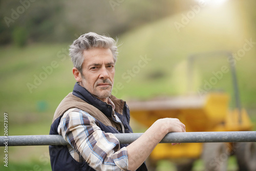 Fotomural Attractive farmer leaning on fence looking at camera