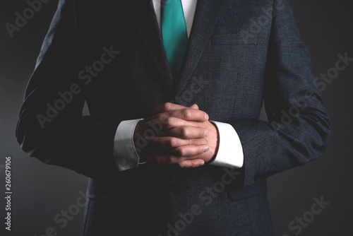 Businessman with a crossed arms on a gray background Canvas Print