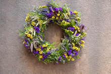 Handmade Wreath Of Purple And Yellow Flowers For Your Home Door Decoration Isolated On A Gray Concrete Background.