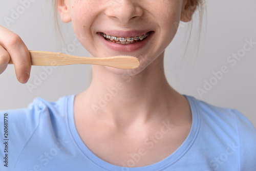 Foto  Smiling teenage girl with dental braces holding toothbrush on grey background
