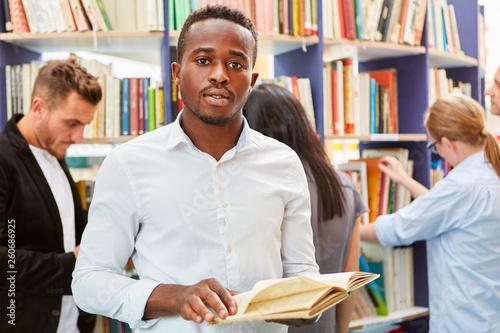 Valokuvatapetti Junger afrikanischer Mann in der Bibliothek
