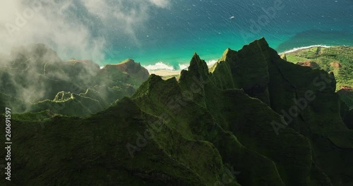Aerial view flying over jungle mountain peaks Na Pali coast Kauai - 260691597