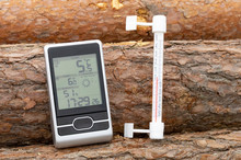 Home Weather Station And Thermometer On The Street On The Background Of Logs