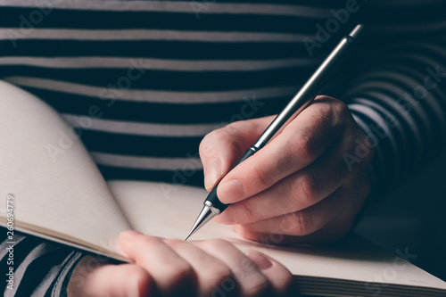 Photo  Left-handed woman writing diary