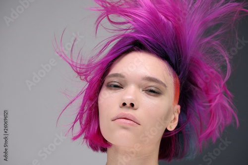Concept Portrait of a punk girl, young woman with chic purple hair color in studio close up on a colorful background with fluttering hair Canvas Print