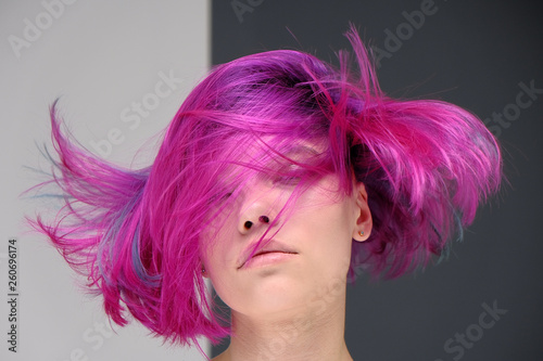 Concept Portrait of a punk girl, young woman with chic purple hair color in studio close up on a colorful background with fluttering hair.