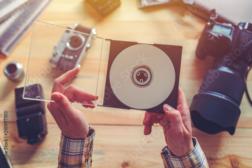 Photographer holding dvd disc with archived photos Wallpaper Mural