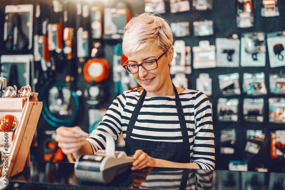 Fototapeta Smiling Caucasian female worker with short blonde hair and eyeglasses using cash register while standing in bicycle store.