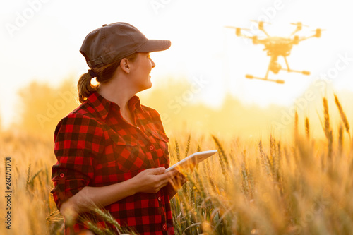 Foto Woman farmer controls drone with a tablet