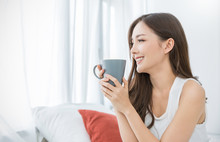 Portrait Of Young Beautiful Asian Woman Hands Holding Coffee Cup Morning Spring Time In White Bedroom. Happy Cheerful Relaxing In Summer. Korean Makeup Wakeup University Lifestyle Concept.