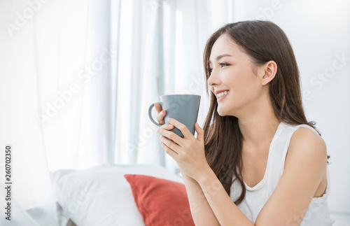 Deurstickers Ontspanning Portrait of young beautiful asian woman hands holding coffee cup morning spring time in white bedroom. Happy cheerful relaxing in summer. Korean makeup wakeup university lifestyle concept.
