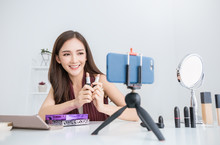 Portrait Of Asian Woman Review Giveaway Product To Fan Following Channel, Recording Video Make Up Cosmetic At Home. Online Influencer Girl Social Media Marketing Live Steaming Smartphone Concept