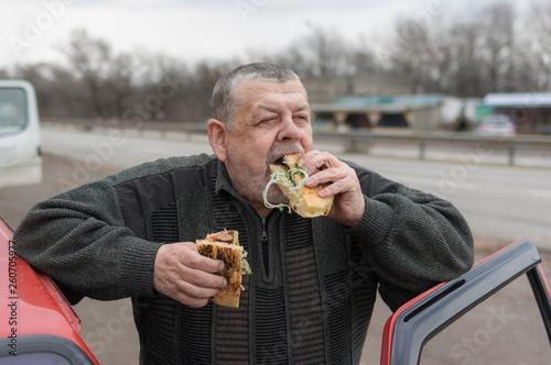 Valokuva  Portrait of Caucasian senior driver gobbling lyulya kebab in lavash near his car