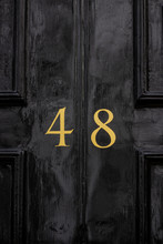Shiny House Door With The Number 48 With The Forty-eight In Bronze Paint