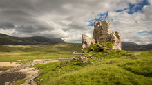 Ardvreck Castle In Scotland On A Green Hill Under Blue Sky With White Clouds
