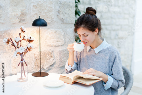 Young woman is drinking coffee and reading book under warm table lamp light. Girl is sitting in cozy modern cafe indoors. - 260716339
