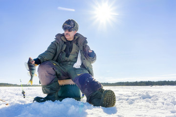 Fototapeta na wymiar fisherman catch on winter fishing