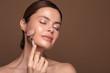 Leinwanddruck Bild - Pleased woman relaxing with rose quartz face roller