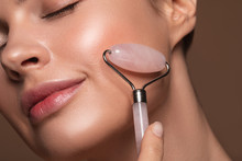 Smiling Woman Using Face Roller On Her Cheek