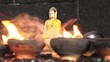 Close up shot of candles with little Buddha statue on the background in Dambulla, Sri Lanka