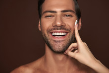 Young Happy Manful Guy Applying Face Cream